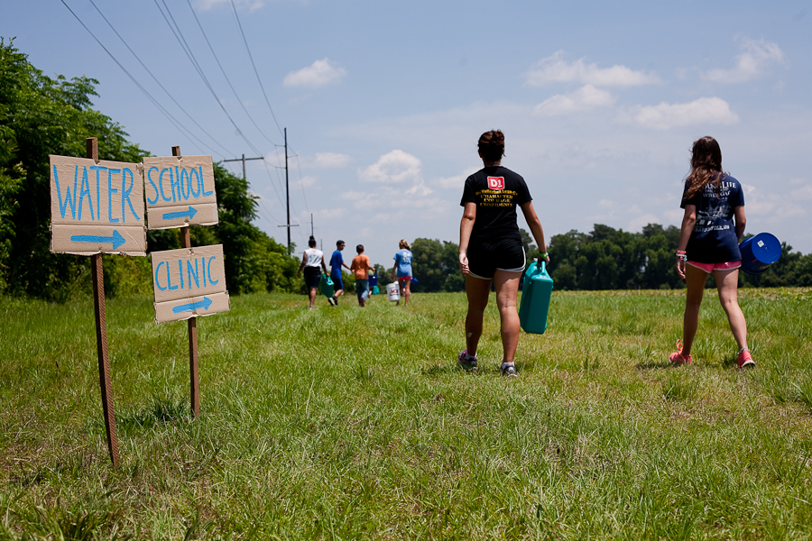 "Students walk a quarter mile to collect water for their ""families."""